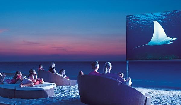 Des personnes assises sur des chaises à la plage regardant un film sur un écran de projection.