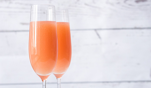 Pair of refreshing Bellinis in champagne flutes