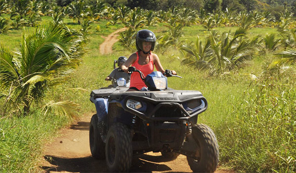 Woman riding an ATV surrounded by lush greenery