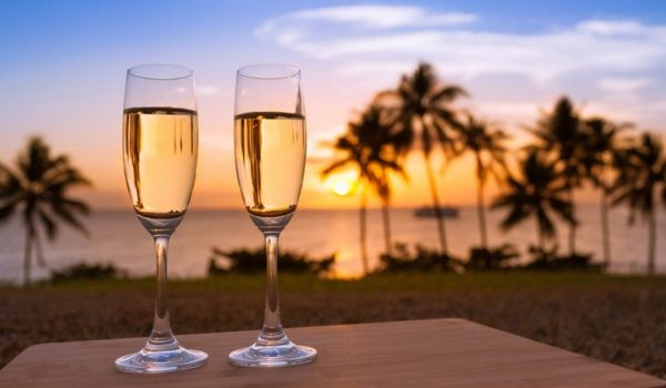 Table with two glasses of champagne overlooking the ocean at sunset