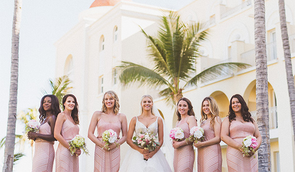 Bride standing with her bridesmaids underneath palm trees
