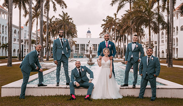 Bride, groom, and groomsmen standing by the pool