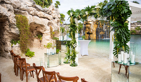 Wedding ceremony by a serene cove with a waterfall