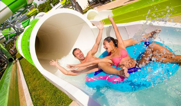 Man and woman riding inner tube down water slide