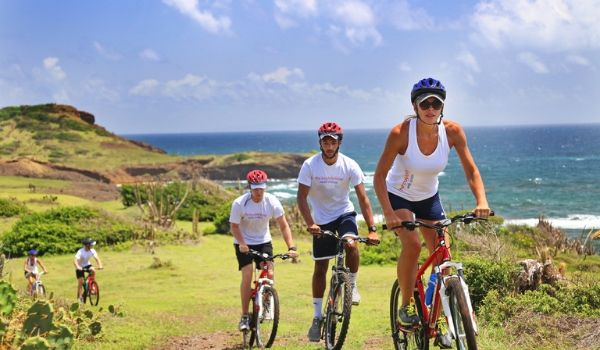 People bike riding up a hill overlooking the coast