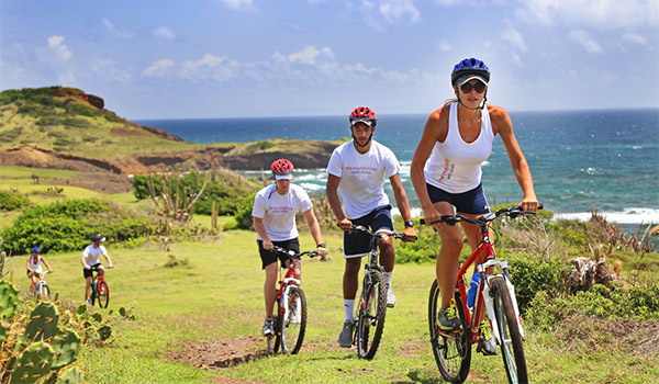 Personnes gravissant en vélo une colline surplombant la côte