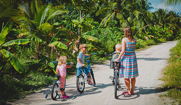 Mother and her three children cycling along a trail lined with palm trees