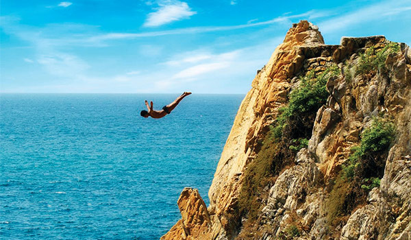 Diver jumping off a high cliff to the ocean below