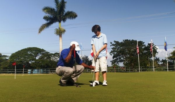 Man teaching a young boy how to golf