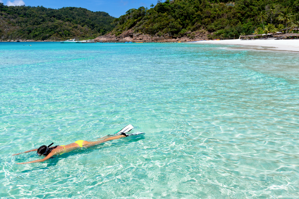 Woman snorkelling in the crystal-clear waters off the beach