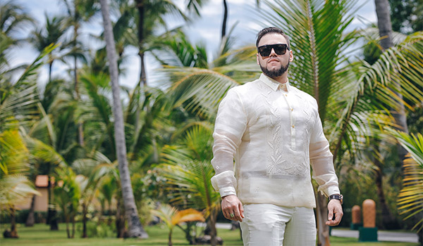 Groom wearing sunglasses and posing in a lush garden