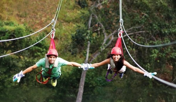 Two kids holding hands while ziplining across the forest