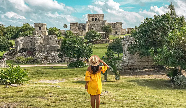 Woman in a dress and hat looking out at ancient Mayan ruins