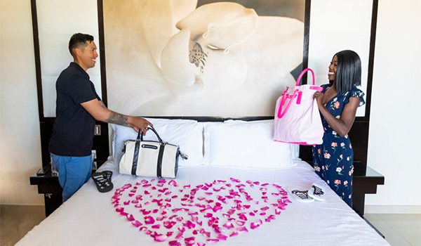 Couple standing next to a bed with rose petals in the shape of a heart