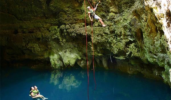 Femme faisant de la spéléologie dans une grotte souterraine inondée