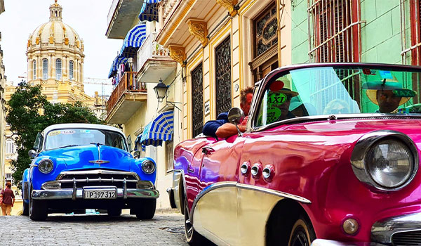 Two classic car driving through the streets of Havana