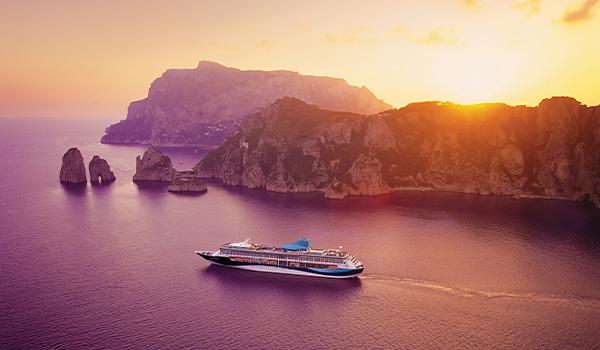 Vue aérienne du bateau de croisière naviguant près de paysages rocheux au coucher de soleil