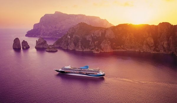 Aerial view of cruise ship sailing by rocky landscapes at sunset