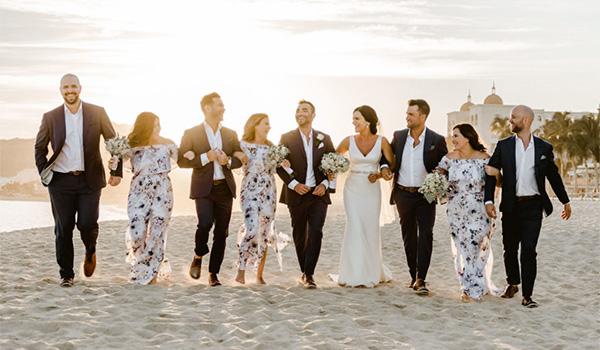Bride, groom, bridesmaids and groomsmen walking arm-in-arm along the beach