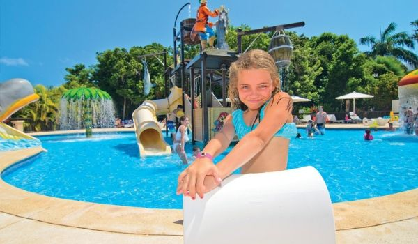 Young girl posing in front of splash park