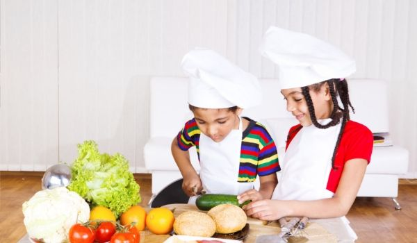 Two young children in chef hats prepping vegetables