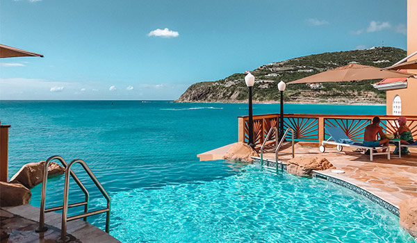 Infinity pool overlooking the breathtaking coast of St Maarten with hills in the background