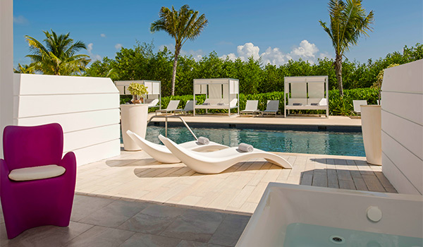 Pool lined with sun loungers overlooking the sea