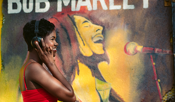 Woman standing in front of a Bob Marley mural