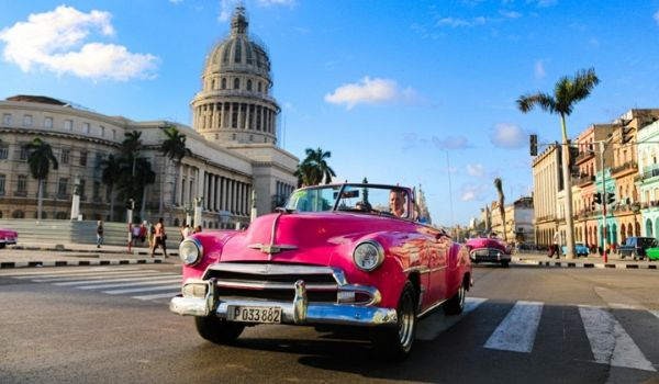 Classic car riding through the streets of Havana