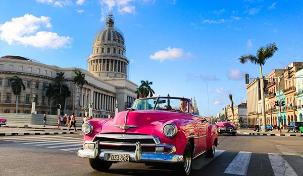 Classic car riding through the streets of Havana