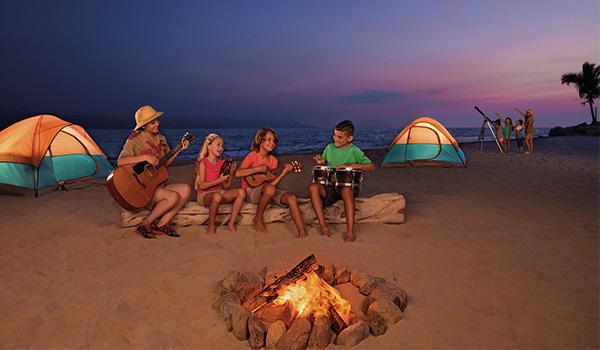 Des enfants assis autour d'un feu de camp sur la plage avec des tentes et un télescope en arrière-plan.