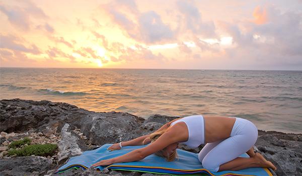 Femme faisant du yoga au bord de la mer