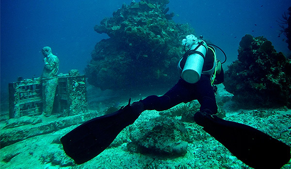 Diver swimming alongside statues at the underwater museum