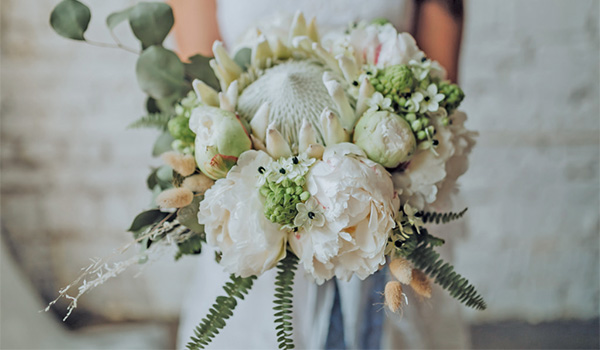 Bride holding a bouquet of white flowers and lush greenery