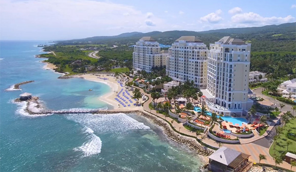 Aerial view of a hotel overlooking the beach with mountains in the background