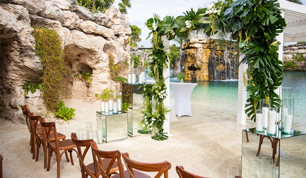 Small wedding ceremony by a cenote with a waterfallo in the background