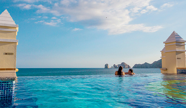 Couple relaxing in an infinity pool overlooking the Arches of Los Cabos