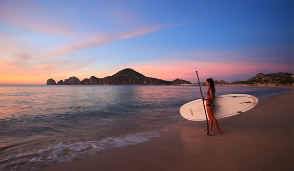 Woman holding a paddleboard at sunset in Los Cabos