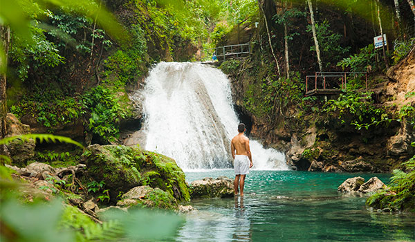 Man standing by a waterfall in the jungle