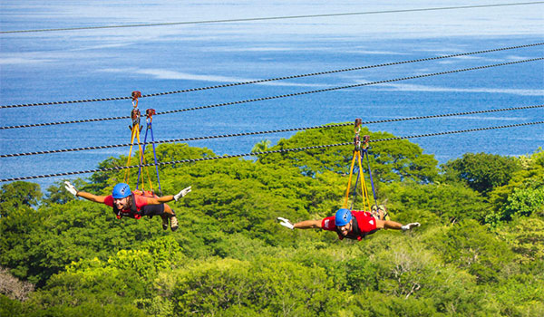 Two people ziplining above the jungle