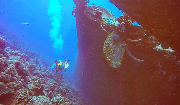 Plongeur nageant à côté de l'hélice d'une épave d'un navire de charge