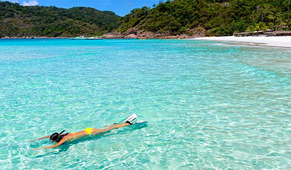Une femme faisant de la plongée avec tuba dans des eaux cristallines de la mer