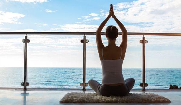 Woman practising yoga on balcony overlooking the ocean