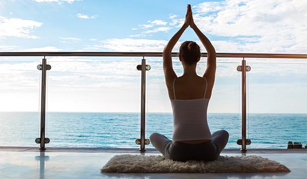 Femme faisant du yoga sur un balcon surplombant la mer