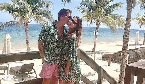 Man kissing a woman on the cheek as they pose by the beach