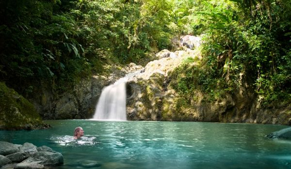 Woman swimming in a serene pool at the bottom of a waterfall