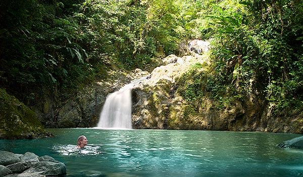 Femme se baignant dans un bassin paisible au pied d'une cascade