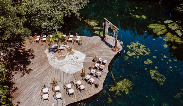 Aerial view of a wedding ceremony on a deck overlooking a cenote