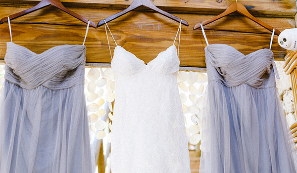 Wedding dress and two bridesmaids dresses on hangars