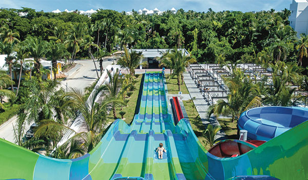 View from the top of a four-lane water slide as a person zooms down to the bottom